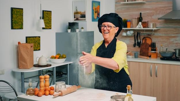 Chef âgé debout dans la cuisine à la maison et cuisinant avec plaisir des produits de boulangerie à base de farine. cuisinier professionnel applaudissant et saupoudrant de mouches en poudre rew ingrédients sur pâte préparant le brea traditionnel