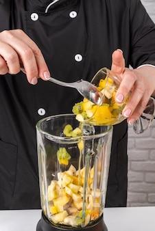 Chef ajoutant des fruits au mélangeur