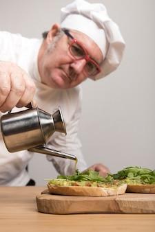 Chef ajoutant de l'huile sur le guacamole