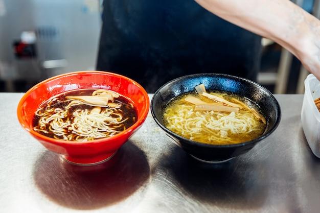 Chef ajoutant des ingrédients dans les nouilles ramen pour faire des ramen au miso et au shoyu.