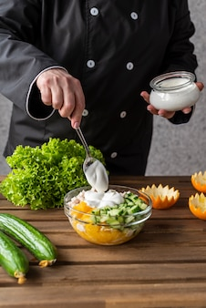 Chef ajoutant la vinaigrette à la salade