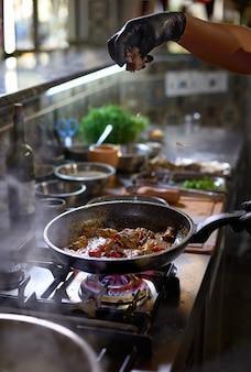 Le chef ajoute les alevins de truffes dans une casserole les tomates et les huîtres,