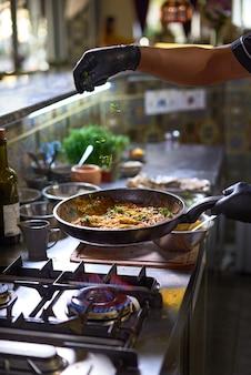 Le chef ajoute des légumes verts frais dans une poêle, des tomates et des huîtres.
