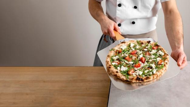 Chef à angle élevé tenant l'outil de peler avec pizza
