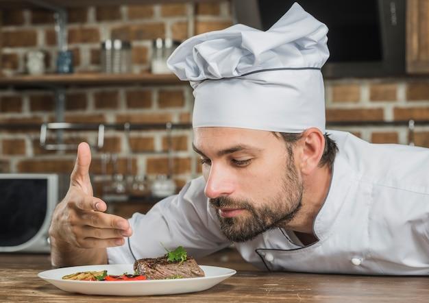 Chef appréciant l'arôme de la nourriture servie sur la plaque