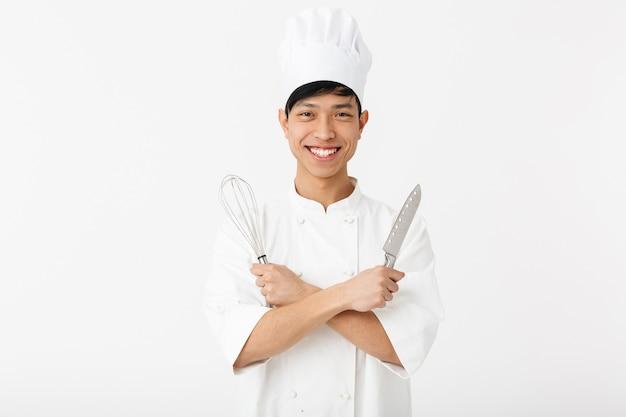 Chef asiatique excité en uniforme debout isolé sur un mur blanc, montrant l'équipement de cuisine