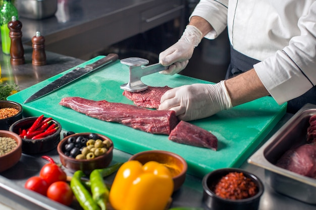 Chef attendrir steak avec attendrisseur de viande sur une planche à découper