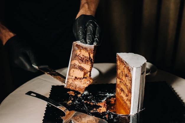Un chef aux gants noirs tranche un gâteau de mariage au chocolat