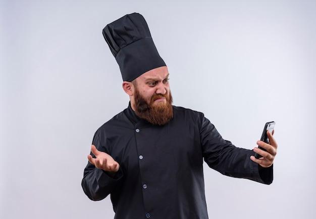 Un chef barbu confus en uniforme noir montrant une expression de colère tout en regardant son téléphone portable sur un mur blanc