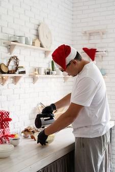 Chef en bonnet de noel la cuisson d'un dessert dans la cuisine