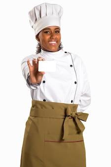 Chef, boulanger ou cuisinier femme montrant une carte vierge portant l'uniforme et un chapeau de chefs. carte vierge pour menu, carte-cadeau, offre, etc. belle femme africaine / noire isolée sur espace blanc