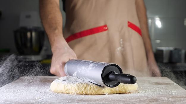 Le chef boulanger met le rouleau à pâtisserie sur la pâte et commence à étaler la pâte sur la table. les mains de l'homme en gros plan.
