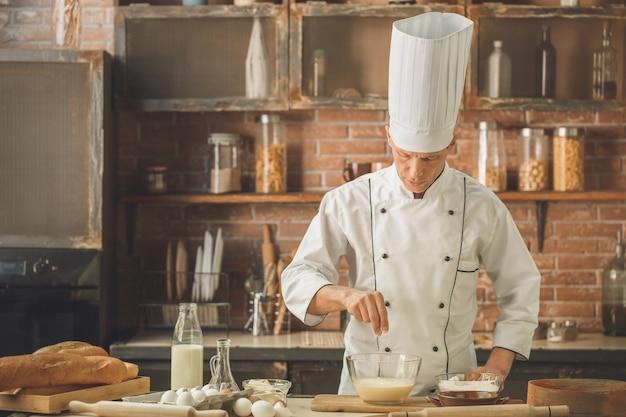 Chef de boulangerie faisant cuire au four dans la cuisine professionnelle ajoutant de la farine