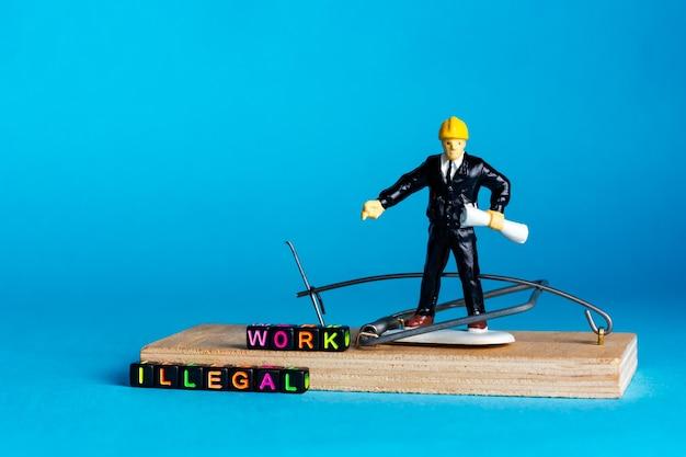 Chef, chef dans une souricière sur fond bleu. inscription de travail illégal. photo de haute qualité
