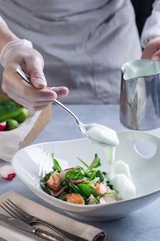 Le chef complète la salade de cuisson et ajoute une sauce blanche au poisson rouge et aux légumes.
