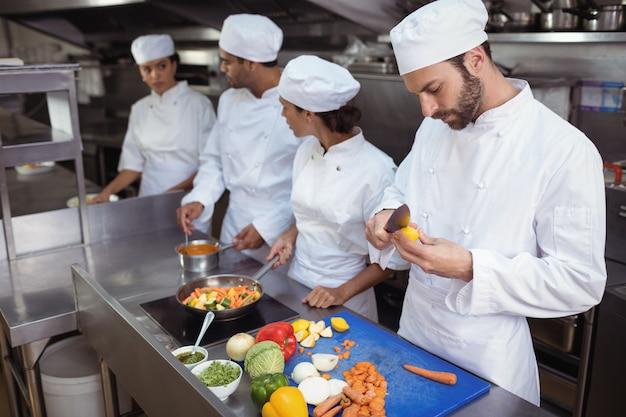 Chef contrôle de la nourriture de la cuillère dans la cuisine au restaurant