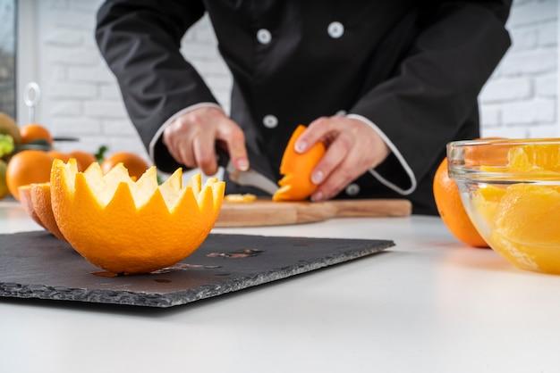 Chef coupant des oranges