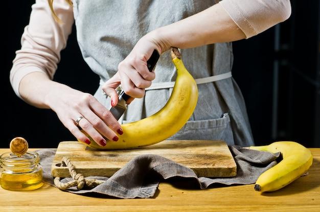 Un chef coupe une banane en tranches. cuisson des bananes cuites au four.