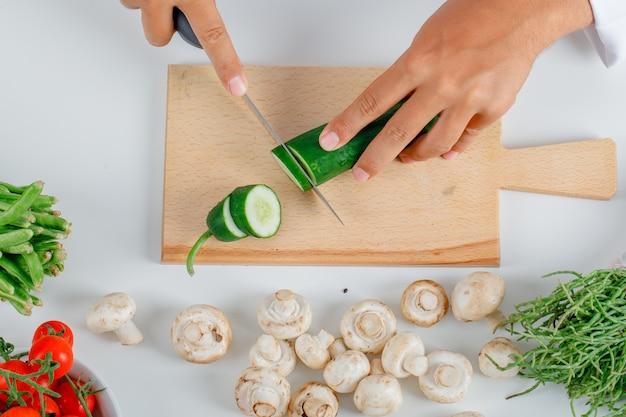 Chef coupe concombre sur planche de bois dans la cuisine en vue de face uniforme.