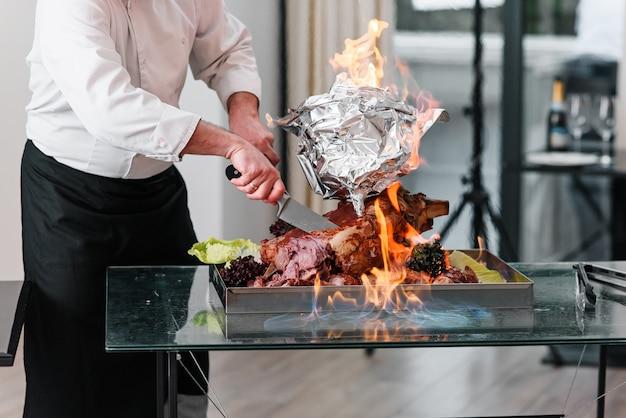 Le chef coupe la dinde cuite au four sur un plateau au feu. dinde rôtie.