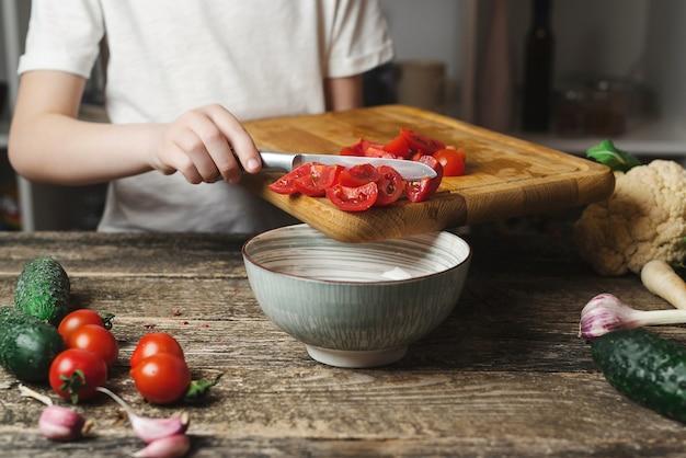Le chef coupe des légumes pour la salade sur une planche à découper. fils préparant des aliments sains pour le dîner en famille. alimentation saine, concept de régime. chef cuisinier à la cuisine.