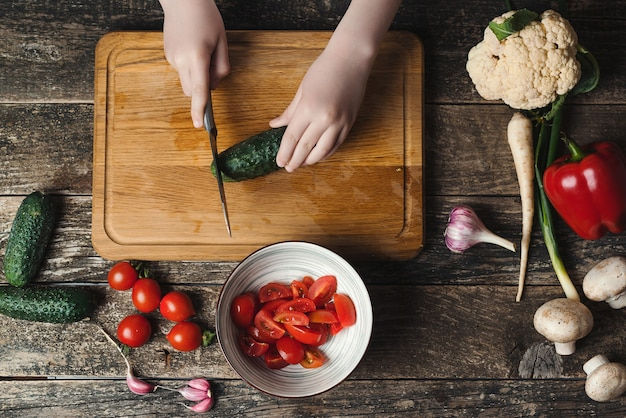 Le chef coupe des légumes pour la salade sur une planche à découper, vue de dessus. fils préparant des aliments sains pour le dîner en famille. alimentation saine, concept de régime. chef cuisinier à la cuisine.