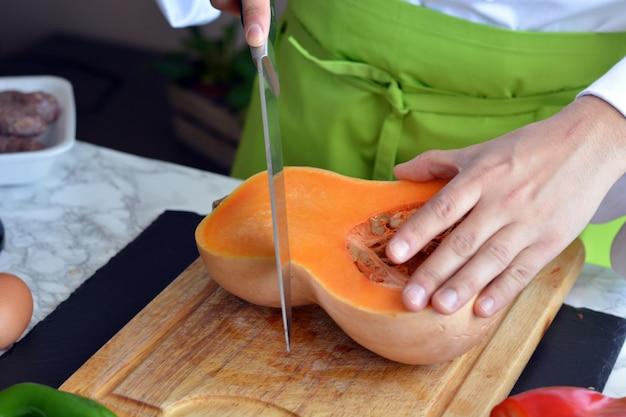 Chef coupe les légumes à la table pour la cuisson