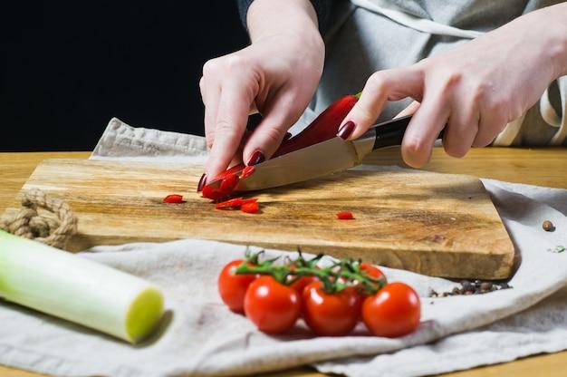 Le chef coupe les piments rouges sur une planche à découper en bois.