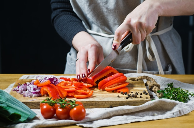 Le chef coupe les poivrons rouges sur une planche à découper en bois.