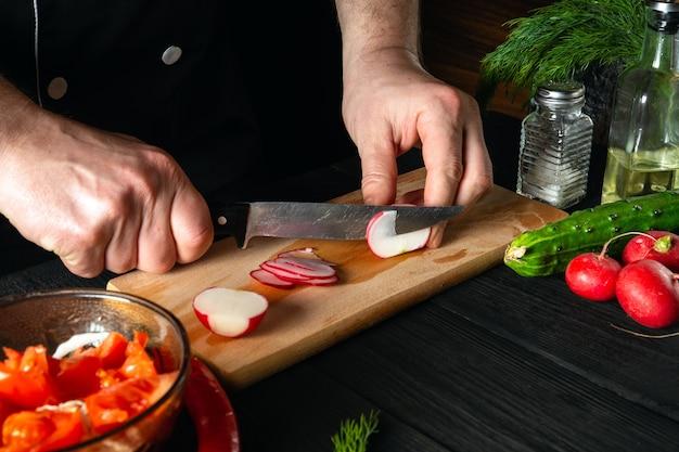 Le chef coupe des radis dans une salade de légumes
