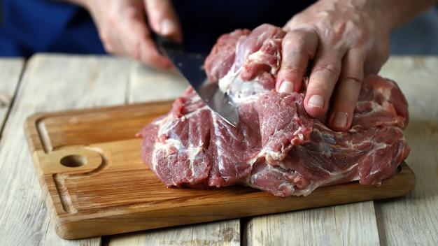 Le chef coupe la viande crue sur la planche à découper