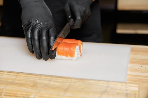 Chef couper avec des rouleaux de saumon couteau