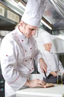 Chef, couper la viande sur une planche à découper, cuisinier professionnel tenant un couteau et couper la viande au restaurant