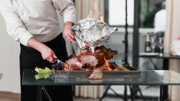 Chef avec un couteau coupe la dinde cuite au four sur un plateau au feu. dinde rôtie.