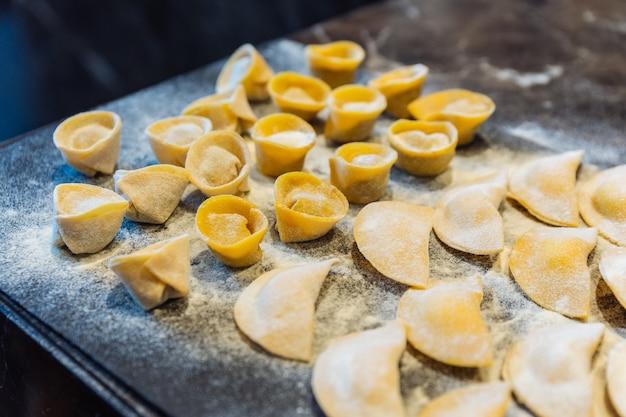 Le chef crée un cercle en forme de ravioli en remplissant la pâte de pâte de sauge et de beurre.