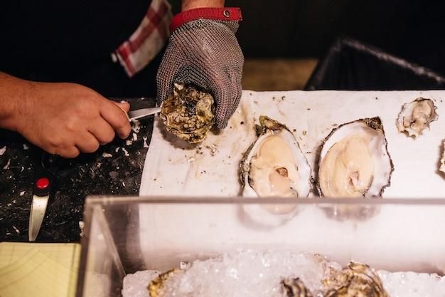 Chef cueillant une huître fraîche avec un couteau et un gant en maille d'acier inoxydable