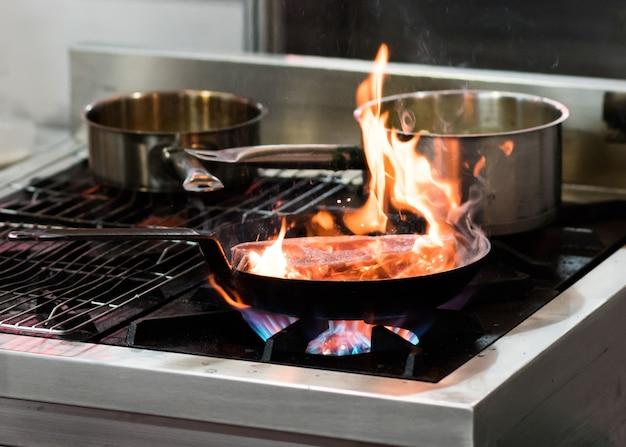 Chef cuisinant avec flamme dans une poêle sur une cuisinière