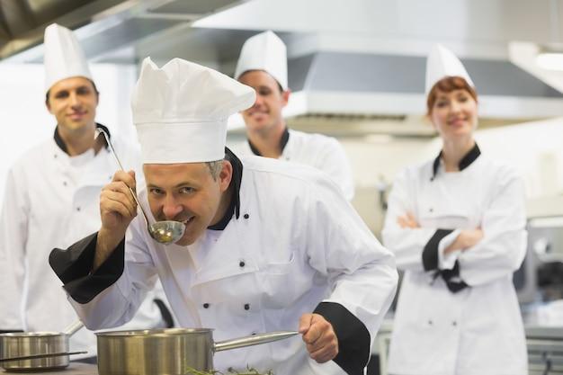 Chef de cuisine dégustation d'une soupe et souriant à la caméra