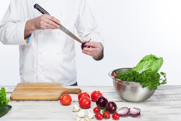 Chef de cuisine salade de légumes frais dans sa cuisine