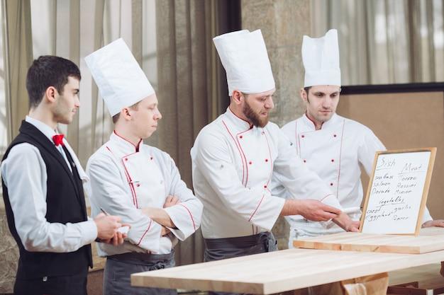 Chef de cuisine et son personnel dans la cuisine. interagir avec dans la cuisine commerciale.