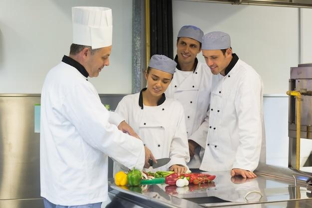 Chef de cuisine souriant, apprendre à couper les légumes
