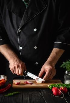 Le chef ou le cuisinier coupe les radis dans une salade de légumes