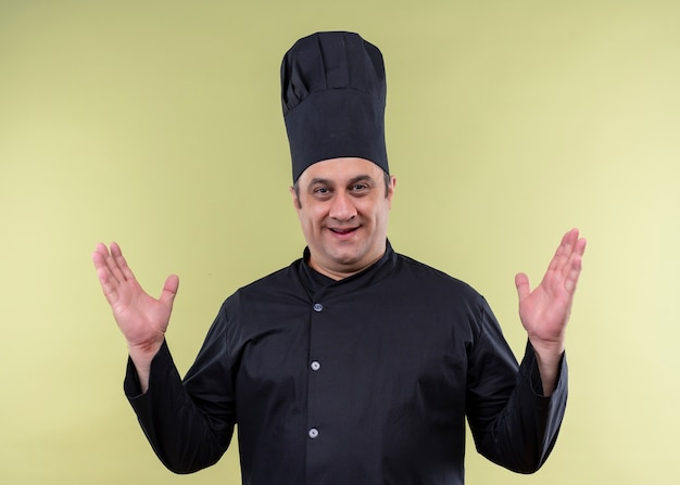 Chef cuisinier mâle portant un uniforme noir et chapeau de cuisinier lookign heureux et positif à la caméra avec les bras levés debout sur fond vert
