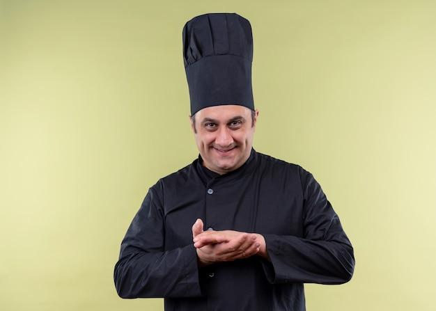 Chef cuisinier mâle portant l'uniforme noir et chapeau de cuisinier regardant la caméra avec sourire sournois tenant la main ensemble debout sur fond vert