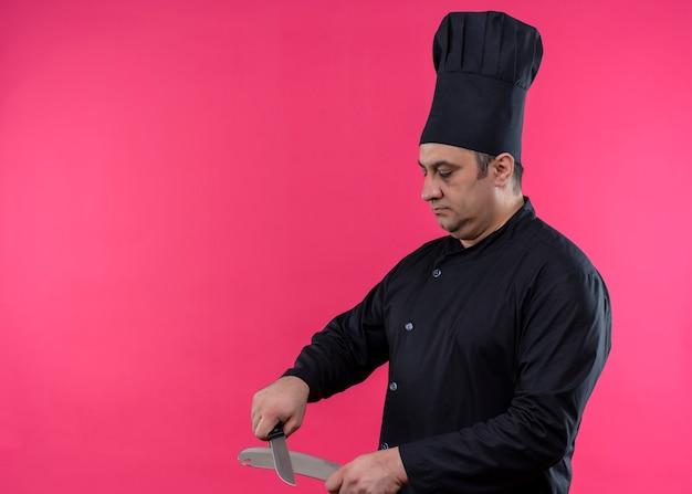 Chef cuisinier mâle portant l'uniforme noir et couteau à aiguiser chapeau avec visage sérieux debout sur fond rose