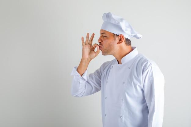 Chef cuisinier masculin faisant un geste savoureux en embrassant les doigts en chapeau et uniforme.