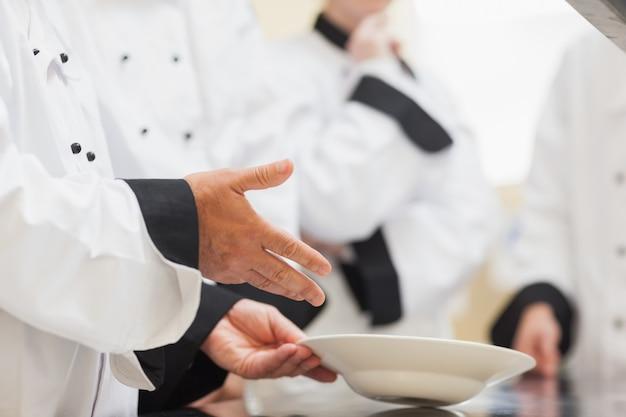 Chef cuisinier montrant un bol à la classe