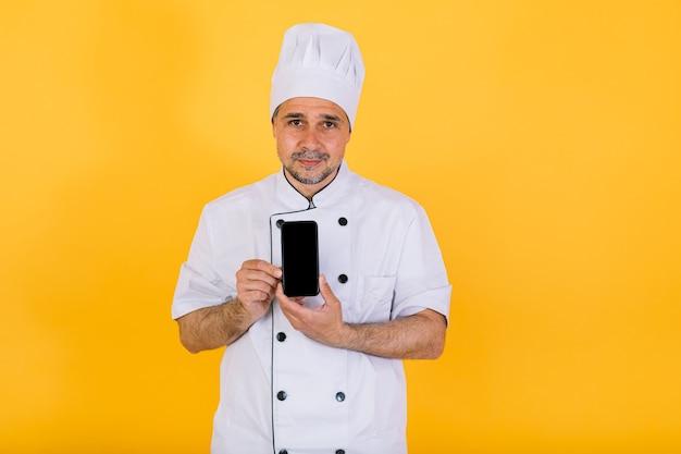 Chef cuisinier portant une casquette et une veste de cuisine blanches, tenant un téléphone intelligent, sur fond jaune