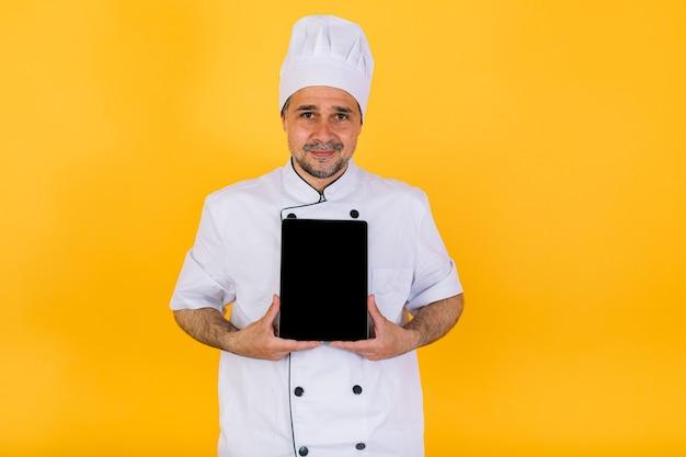 Chef cuisinier portant une veste et un chapeau de cuisine blancs, tenant une tablette et pointant un doigt, sur fond jaune