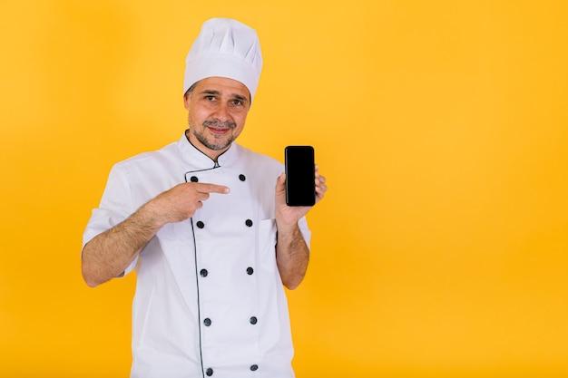 Chef cuisinier portant une veste et un chapeau de cuisine blancs, tenant un téléphone intelligent et pointant un doigt, sur fond jaune